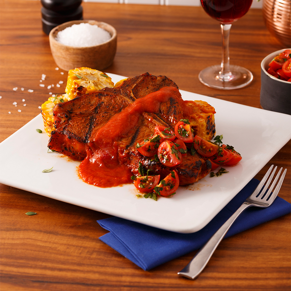Biftecks d'aloyau de veau de grain du Québec, sauce flambée au bourbon avec concassé de tomates et fines herbes