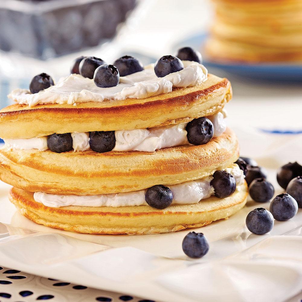 Pancakes garnis de crème à la vanille et de bleuets