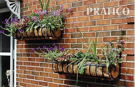 Des boîtes à fleurs sur un mur de briques